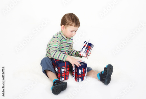 boy sits and plays with gift boxes