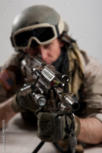 Soldier with rifle against white background.