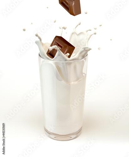 Leinwandbild Motiv Chocolate cubes splashing into a milk glass. On white background