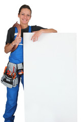Smiling female plumber with panel for message