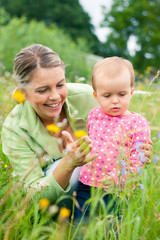 Young mother and her baby girl playing outdoors