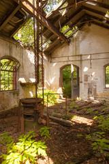 Ein altes halb verfallenes Gebäude steht in einem Wald