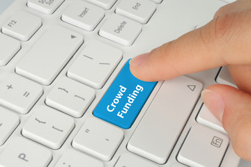 Hand pushing blue crowd funding button on keyboard