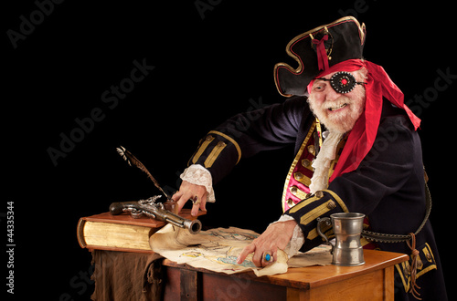 Happy old pirate captain pointing at his treasure map