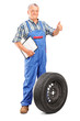 Full length portrait of a mature mechanic with tyre