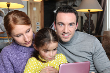 Family gathered on sofa with pink laptop