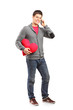 Male holding a heart shaped pillow and talking on a phone
