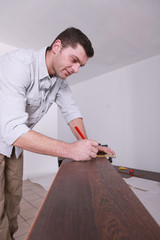 Man marking parquet floor before cutting to size