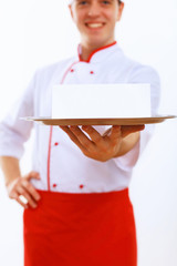 Cook holding an empty tray