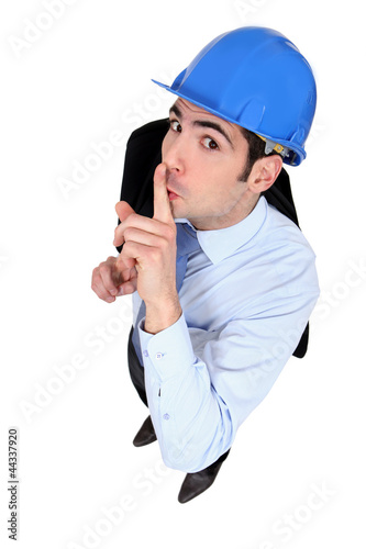 Engineer holding his finger to his lips