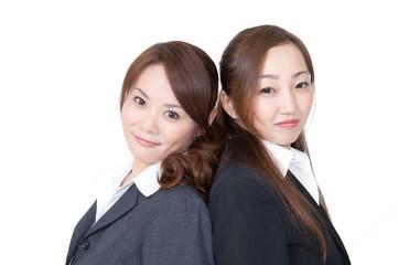 オフィスで女性二人が背中合わせにしている素材