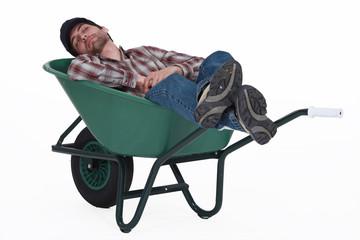 Worker taking a nap in wheelbarrow