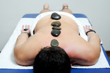 Man relaxing on massage bed with hot stones