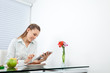 Businesswoman At Breakfast Table Using Tablet PC