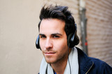 Portrait of attractive man in urban background listening to the