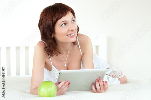 woman with an green apple and tablet at bed reading ebook