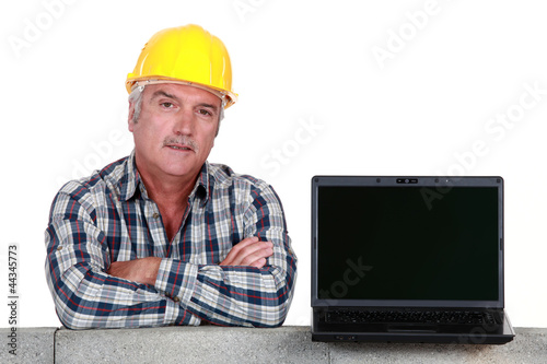 Artisan resting on concrete wall with computer