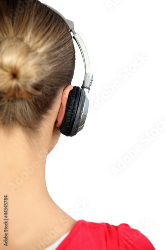 Girl listening to music with headphones, back view
