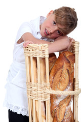 little girl dressed in baker reposing on a bread bin
