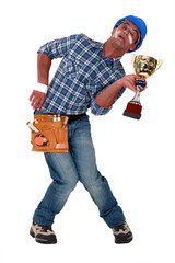 Accident prone construction worker holding a trophy