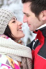 Happy couple kissing in the snow