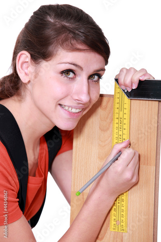 Female carpenter marking out wood with set-square