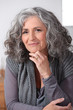Grey-haired woman touching chin