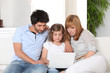 Young family gathered on the sofa with laptop