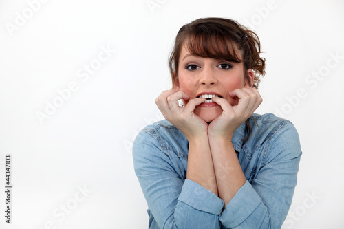 Woman biting her nails.