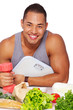 Portrait of muscle man smiling in kitchen with food