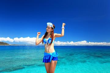 澄んだ珊瑚礁の海と水着姿の女性