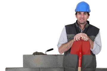 Stonemason standing proudly next to his work