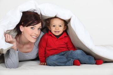 Woman and little boy hiding under a duvet