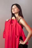 woman which tries on red shirt in shop