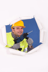 Manual worker with drill tearing through poster