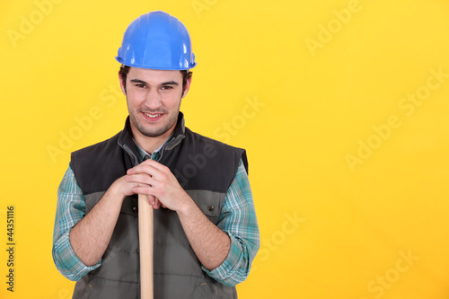 Man leaning on sledge-hammer handle