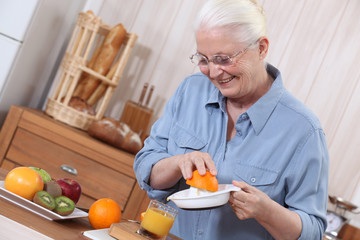 Elderly lady squeezing orange juice