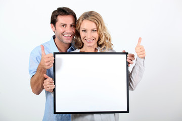 woman and man holding board