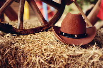 on a haystack the brown cowboy's hat and a wooden wheel lies