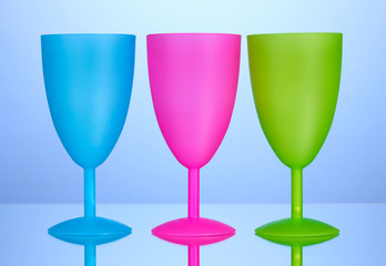 Bright plastic goblets on blue background