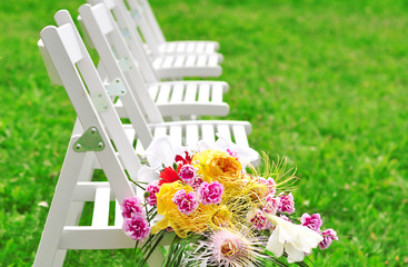 A number of white chairs and a bouquet of flowers.