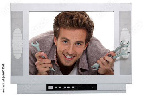 man poking his head through a mock up TV set