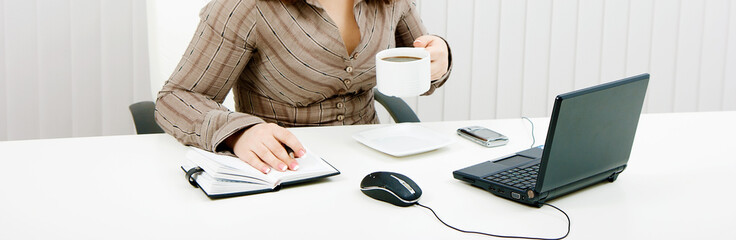 woman drinking coffee at work with