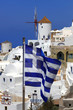 Santorini with windmill and flag of Greece