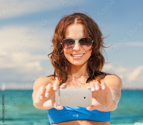 happy woman with phone on the beach