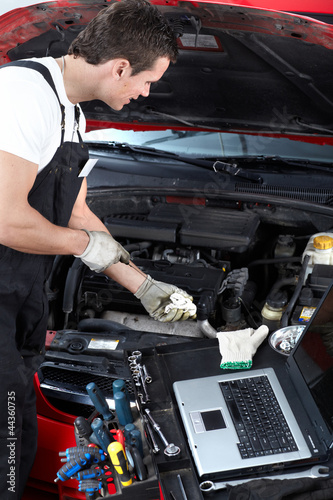 Auto mechanic checking oil.