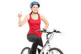 A bicyclist posing on a bicycle and giving a thumb up