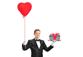 A waiter holding a red heart shaped balloon and a gift