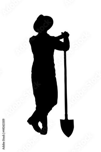 Silhouette of a male farmer holding a shovel
