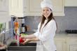 Happy female chef washing vegetables